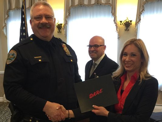 Montgomery Police Officer Bruce Heddy receives his DARE Officer certification from his training mentor, Officer Kate Proscia of the Branchburg Police Department. In the background is Rafael Morales of DARE America.