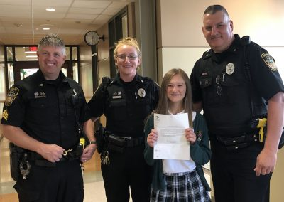 3rd place: Grier Primrose (St. Kilian Catholic School). Grier received a Certificate for one day for a Family of Four to the Pittsburgh Zoo, a $20.00 gift card for Playthings, Etc., and a $5.00 Gift Certificate for King Cone Ice Cream. In photo: Sgt. Harry Callithen, Deputy Rachel Sporrer, Grier Primrose, Deputy Anthony Sawl.