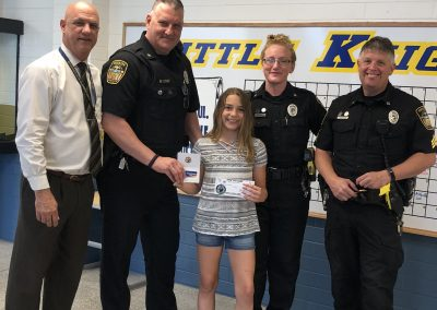 4th Place: Danielle Golden (South Butler Intermediate). Danielle received a $20.00 gift card for Playthings Etc., and a $5.00 Gift Certificate for King Cone Ice Cream. In photo: Principal Frank Moxie, Deputy Anthony Sawl, Danielle Golden, Deputy Rachel Sporrer, Sgt. Harry Callithen.